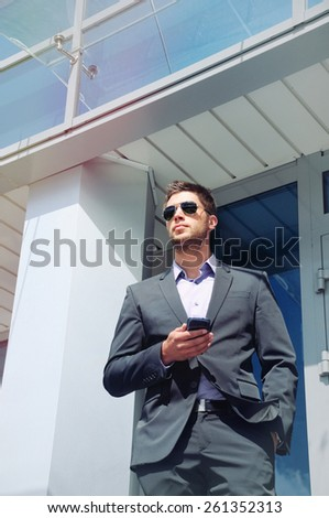 attractive young businessman with phone device in hands on office building background, business concept - stock photo