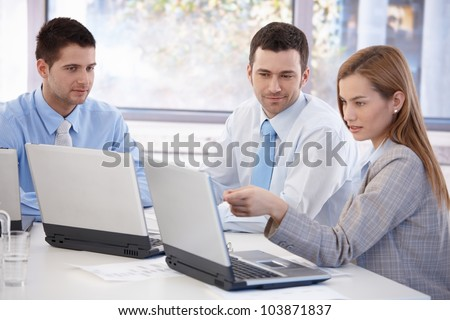Attractive young businesspeople working together in bright office, smiling. - stock photo