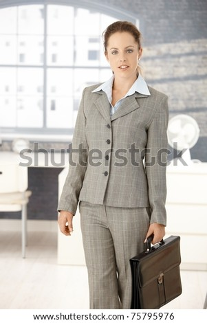 Attractive young businesswoman arriving to office in the morning, holding briefcase.? - stock photo