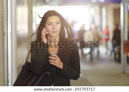 Attractive Young Businesswoman Calling on Mobile Phone, Walking Inside the Mall While Holding a Cup of Coffee. - stock photo