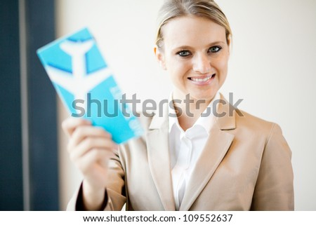 attractive young businesswoman holding air ticket - stock photo