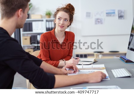 Attractive young businesswoman in a discussion with a male colleague listening to him as she sits at the desk with a journal taking notes - stock photo