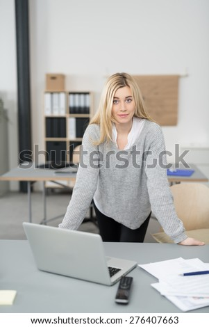 Attractive young businesswoman in an open-plan office standing leaning on her desk looking at the camera with a friendly smile - stock photo