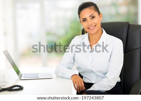attractive young businesswoman in office looking at the camera - stock photo
