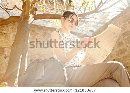 Attractive young businesswoman reading a financial newspaper while sitting down on a stone wall in a park with direct sun rays filtering through. - stock photo