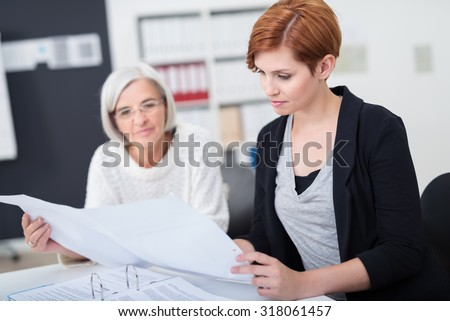 Attractive Young Businesswoman Reviewing Some Business Documents with her Senior Colleague Inside the Office. - stock photo