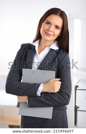 Attractive young businesswoman standing near desk with folder in the office - stock photo