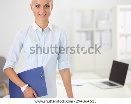 Attractive young businesswoman standing near desk with folder in the office. - stock photo