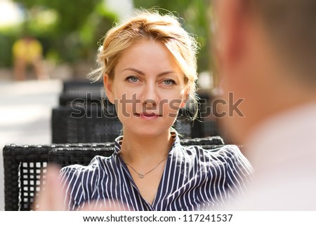 Attractive young businesswoman talking with senior businessman at business lunch outdoors - stock photo
