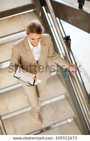 attractive young businesswoman walking down stairs - stock photo