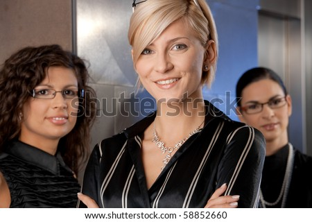 Attractive young businesswomen, waiting for lift in office lobby, talking. - stock photo