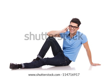 Attractive young casual man laying on the floor, speaking on the phone and smiling to the camera - stock photo