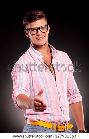 attractive young casual man offering to shake hands and smiling, on black background - stock photo