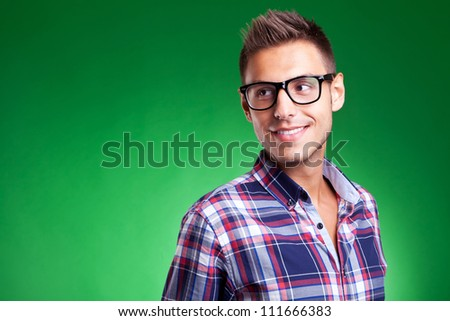 Attractive young casual man wearing glasses and looking away, against green background - stock photo