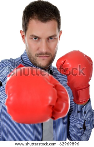Attractive young caucasian businessman wearing boxing gloves. Blow with right arm. Focus on man. Studio shot. White background. - stock photo