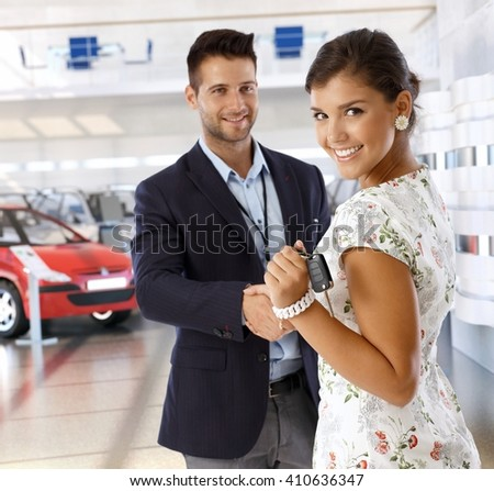 Attractive young caucasian casual businesswoman shaking hands with car dealer wearing suit at business dealership saloon, Looking at camera, smiling, standing, handing over keys. - stock photo