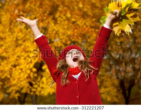 attractive young caucasian little girl in warm red colorful clothing  on yellow leaves outdoors smiling happy child kid walk looking up - stock photo