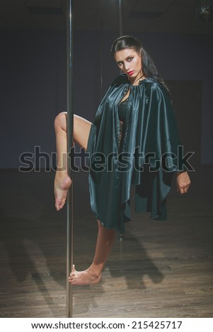 Attractive young caucasian woman dancing near the pole. - stock photo