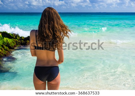 Attractive young caucasian woman in black swimsuit looking on sea at tropical beach - stock photo