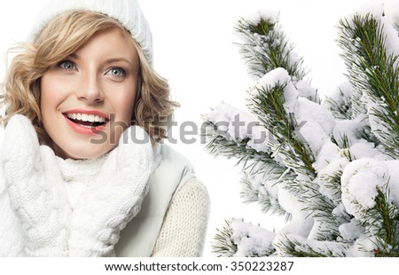 attractive young caucasian woman in warm clothing  in studio isolated on white smiling christmas tree covered with snow - stock photo