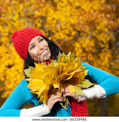 attractive young caucasian woman in warm colorful clothing lying down on yellow leaves outdoors smiling - stock photo
