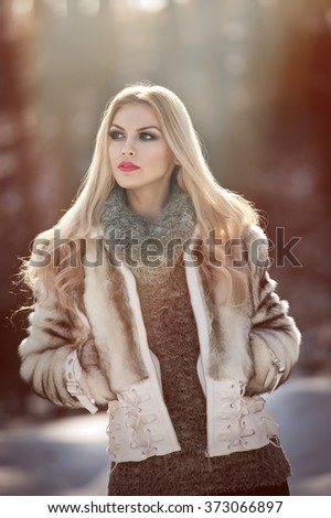 Attractive young Caucasian woman with short fur jacket in winter park. Beautiful blonde girl with gorgeous eyes and long hair, outdoor shot in bright cold day, makeup - sensual female art portrait - stock photo