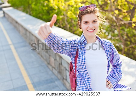 Attractive young confident smiling woman student in casual clothes showing thumb up gesture outdoor. Good for study courses and student exchange program posters and advertising - stock photo
