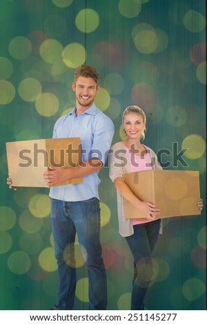 Attractive young couple carrying moving boxes against close up of christmas lights - stock photo