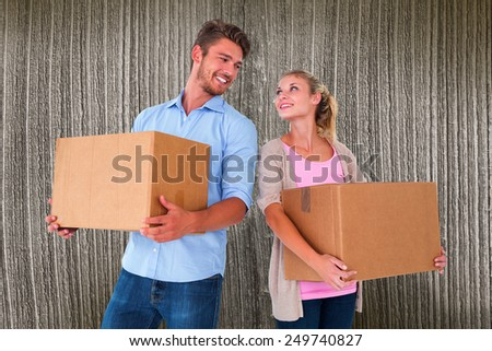 Attractive young couple carrying moving boxes against wooden planks - stock photo