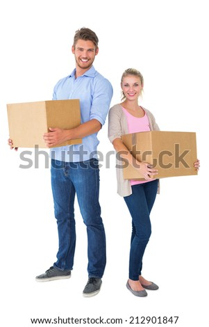 Attractive young couple carrying moving boxes on white background - stock photo