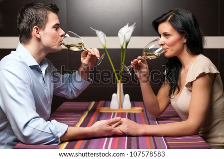 Attractive young couple drinking wine and flirting - stock photo