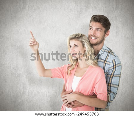 Attractive young couple embracing and looking against white background - stock photo