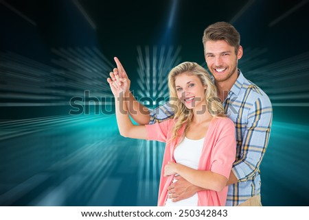 Attractive young couple embracing and pointing against cool nightlife lights - stock photo