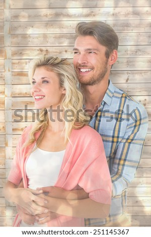 Attractive young couple embracing and smiling against light glowing dots design pattern - stock photo