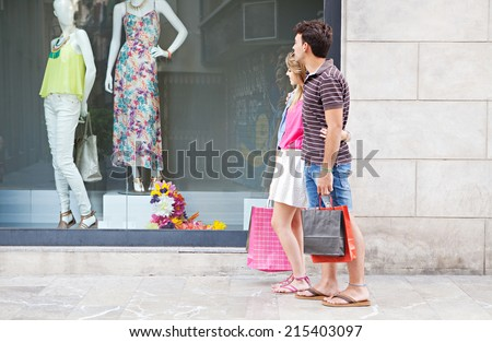 Attractive young couple enjoying a vacation city break together, walking by a fashion store shop window with manikins and clothing, smiling while shopping outdoors. Consumer and travel lifestyle. - stock photo