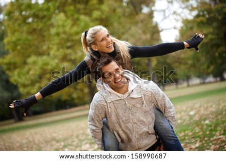 Attractive young couple having fun in autumn park, boy carrying girl piggyback. - stock photo