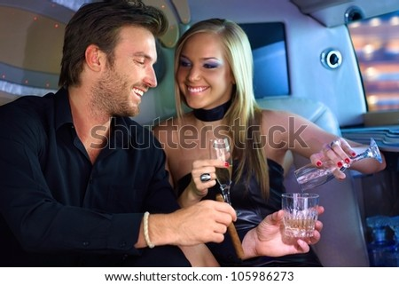 Attractive young couple having fun in limousine, drinking. - stock photo