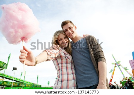 Attractive young couple holding each other and having fun in an attractions park arcade, holding a cotton candy sweet and smiling. - stock photo
