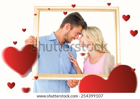 Attractive young couple holding picture frame against hearts - stock photo
