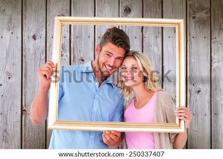Attractive young couple holding picture frame against wooden planks - stock photo