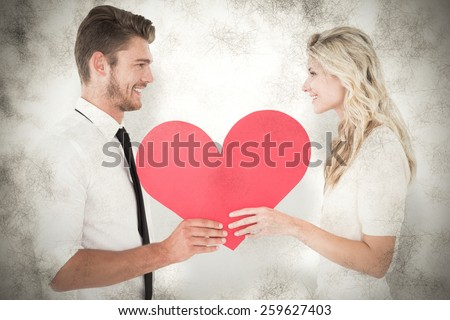 Attractive young couple holding red heart against grey background - stock photo