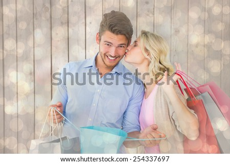 Attractive young couple holding shopping bags against light glowing dots design pattern - stock photo