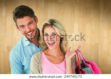 Attractive young couple holding shopping bags against wooden planks - stock photo