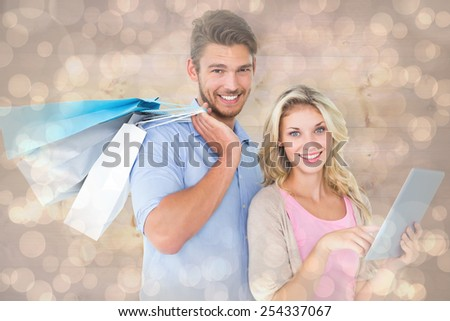 Attractive young couple holding shopping bags using tablet pc against light glowing dots design pattern - stock photo