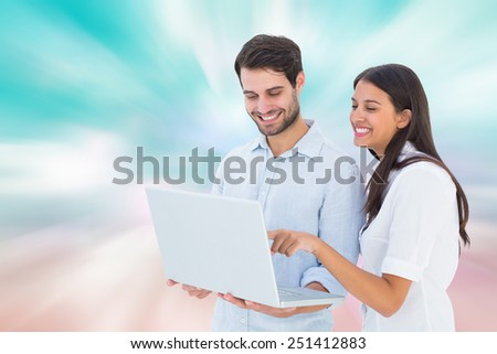 Attractive young couple holding their laptop against digitally generated pink and blue girly design - stock photo