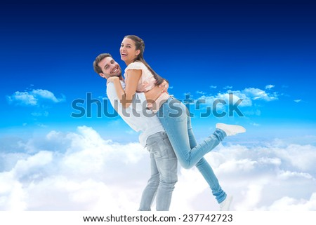 Attractive young couple hugging each other against bright blue sky over clouds - stock photo