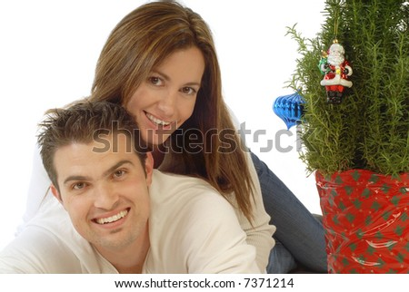 Attractive young couple hugging, full of Christmas cheer; isolated on white - stock photo