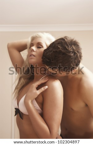Attractive young couple in bedroom kissing - stock photo
