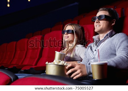 Attractive young couple in 3D glasses watching movies in cinema - stock photo