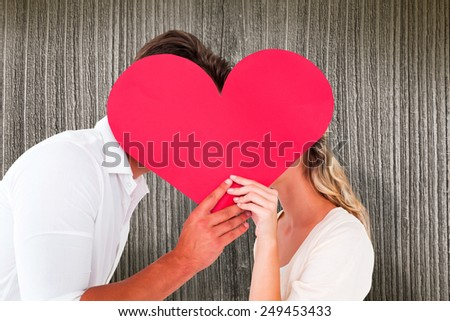 Attractive young couple kissing behind large heart against wooden planks - stock photo